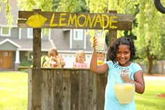 Girl in front of lemonade stand